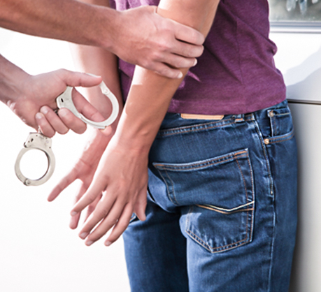 man with hands behind his back and handcuffs on